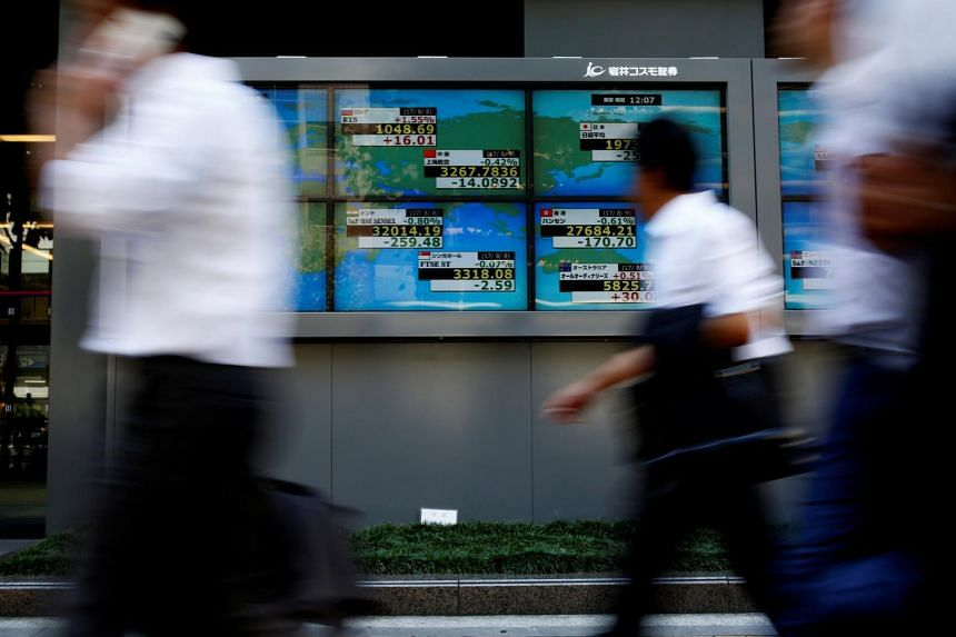People walk past an electronic board showing Japan's Nikkei average outside a brokerage at a business district in Tokyo, on Aug 9, 2017.
