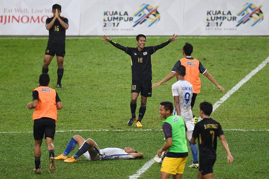 Thailand's players celebrate after defeating Malaysia during their men's football final match of the 29th Southeast Asian Games (SEA Games) at Shah Alam Stadium.