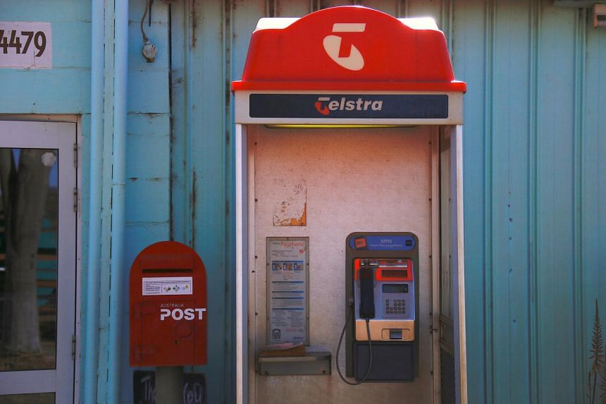 A Telstra public phone booth can be seen outside the post office in the town of Cooladdi, located west of Brisbane in Queensland, Australia.