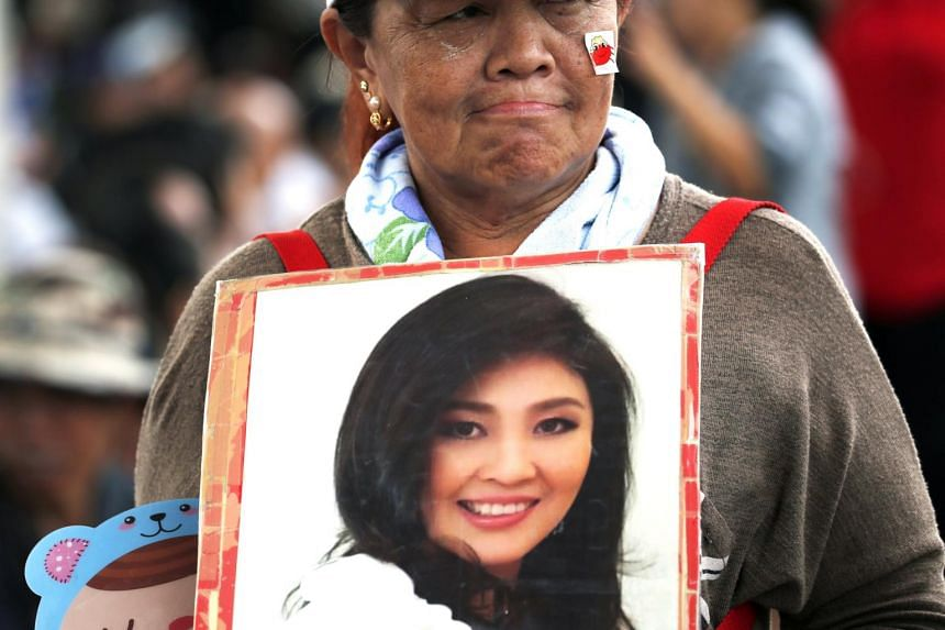A supporter holds a photograph of former prime minister Yingluck Shinawatra after she failed to appear to hear her verdict at the Supreme Court's Criminal Division for Persons Holding Political Positions in Bangkok, on Aug 25, 2017.