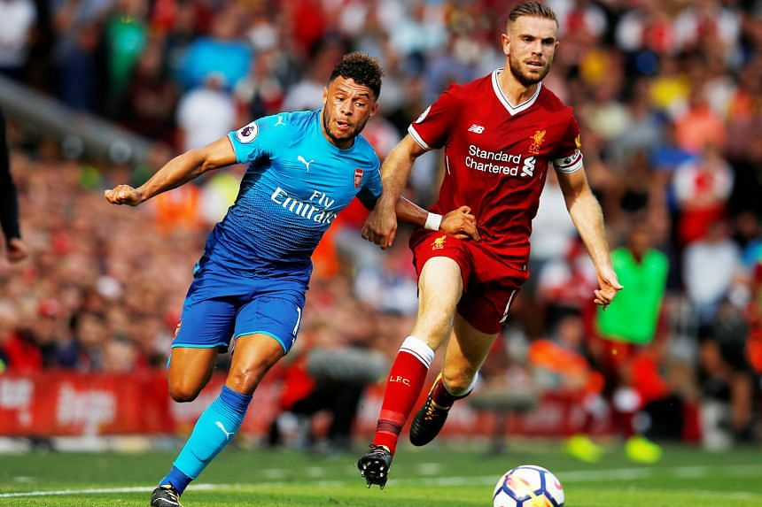 Arsenal's Alex Oxlade-Chamberlain playing as a right wing-back at Anfield as he challenges Liverpool captain Jordan Henderson for the ball. The 24-year-old England international can also play anywhere in midfield.