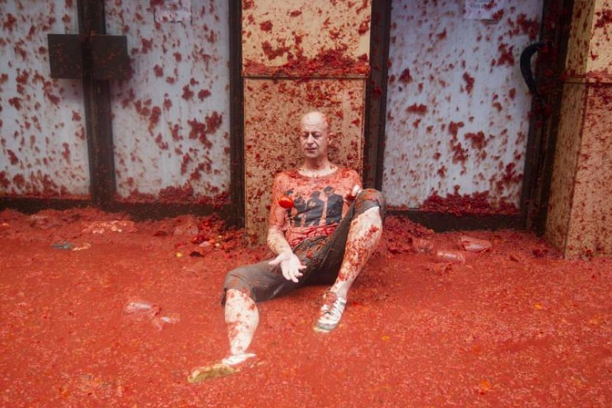 """A reveller covered in tomato pulp takes part in the annual """"Tomatina"""" festival in the eastern town of Bunol, on Aug 30, 2017."""