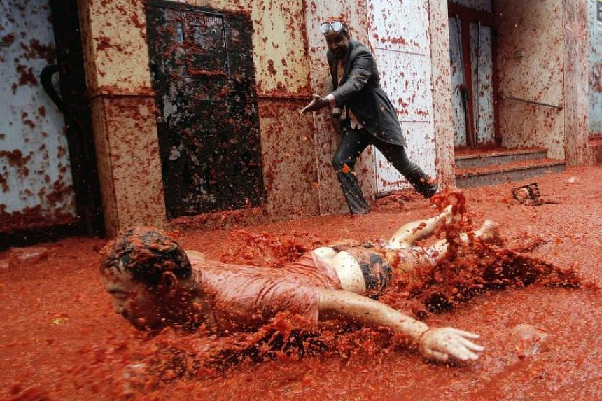 A man slides on the pavement covered with squashed tomatoes as he takes part in the traditional tomato fight called 'Tomatina' in Bunol, Spain, Aug 30, 2017.