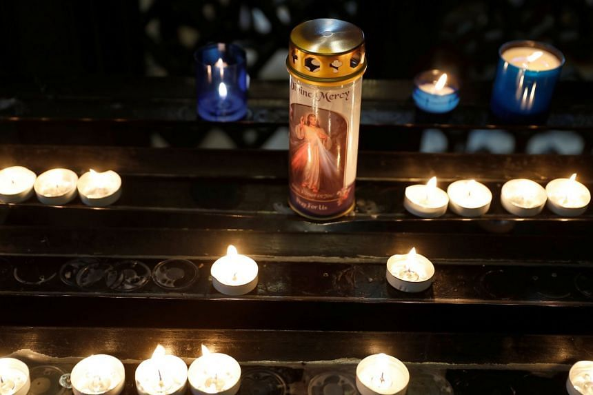 Worshippers' candles burn inside Westminster Cathedral in London, Aug 20, 2017.