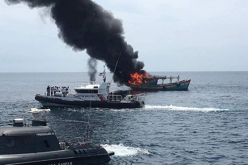 Malaysia's coast guard burning a fishing boat caught in its waters yesterday.