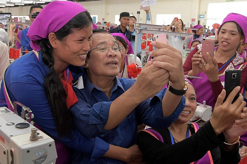 Mr Hun Sen taking a wefie with workers at a factory compound on the outskirts of Phnom Penh yesterday.