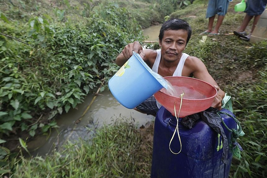 A villager collecting water from a river in Cibarusah in Indonesia's West Java province on Tuesday. The dry weather started last month and is expected to be at its worst next month and last until October.