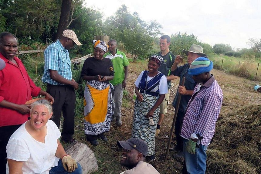 """Migrants from the landlocked country of Burundi, in central Africa, at a composting workshop with locals in the regional city of Mildura, in south-east Australia. Mainly refugees, they are farming on land - """"dead land"""" ravaged by drought - donated by"""