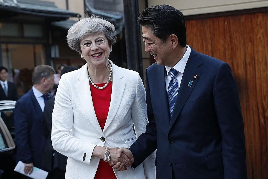Japan's PM Shinzo Abe welcoming his British counterpart Theresa May as she arrived for a tea ceremony in Kyoto yesterday. Mrs May, who is in Japan on a three-day visit, will hold a summit with Mr Abe in Tokyo today. They are expected to discuss issue