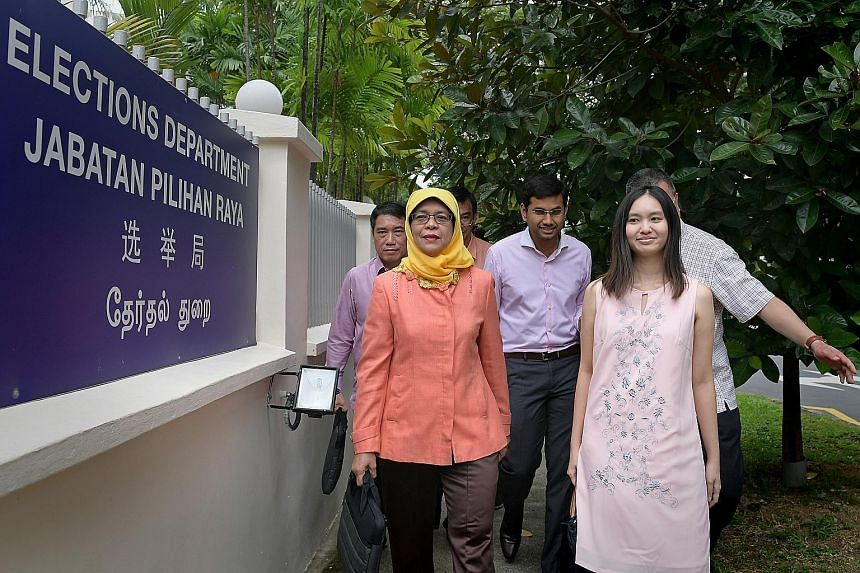 Madam Halimah Yacob arriving at the Elections Department yesterday with election agents Florina Oo and Mohamed Irshad (centre), as well as principal election agent Lawrence Leow (far left).