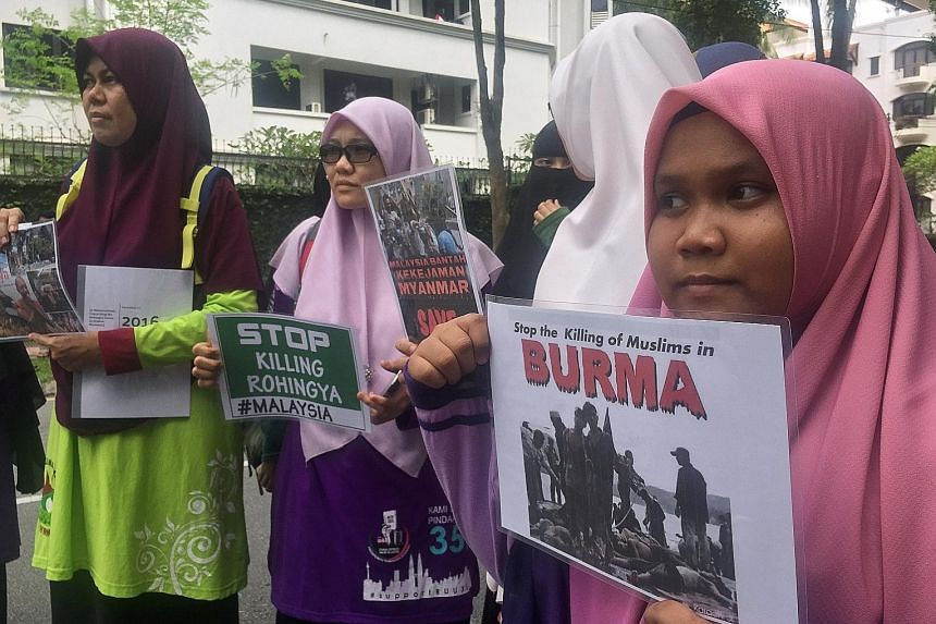 Protesters holding placards near the Myanmar embassy in Kuala Lumpur yesterday. They demanded that Myanmar stop the violence against the minority Rohingya community.