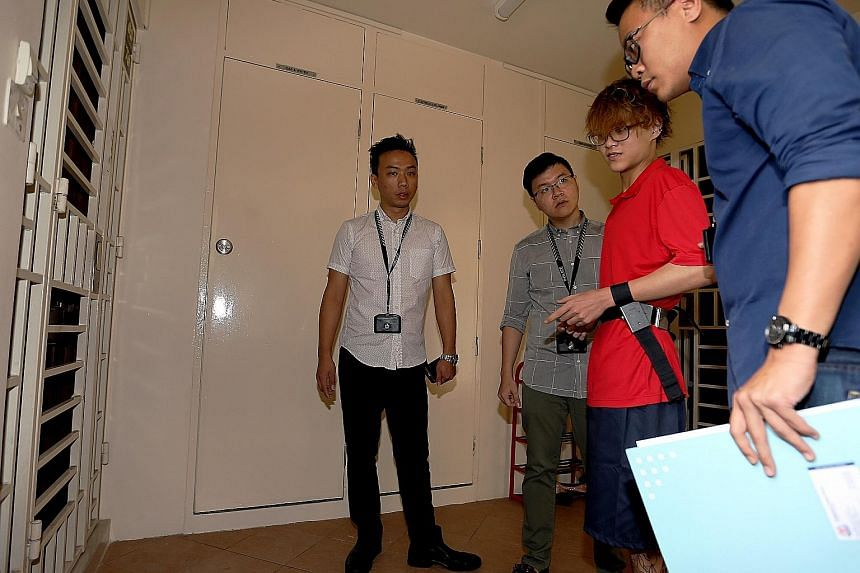 Joven Bey Ding Hui (in red), 16, being accompanied by police officers to a flat in Redhill. He is suspected of setting fire to the front door of three homes in Redhill, Paya Lebar and Bedok. He is also believed to be responsible for loan-shark harass