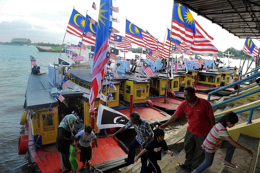 Terengganu state ferries bedecked with Malaysian flags, ahead of the country's national day, at the Seberang Takir jetty. The ferries had participated in a 16-boat event earlier to sail along Sungai Terengganu.
