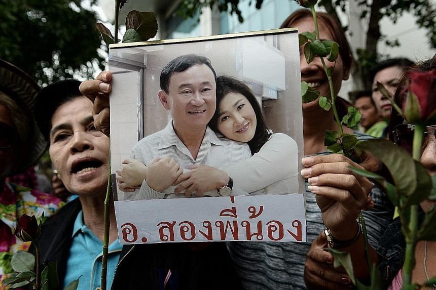 A woman holding an image of former Thai prime minister Yingluck Shinawatra and her brother Thaksin, in this photo taken on Aug 5, before Yingluck arrived at the Supreme Court in Bangkok for her criminal negligence case.