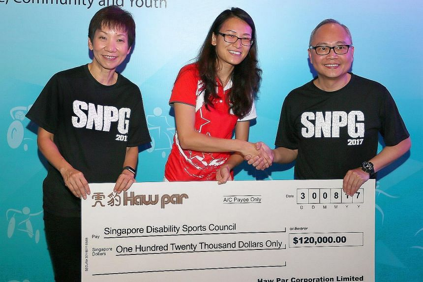 Kelly Fan, Singapore Disability Sports Council executive director (centre), receiving the $120,000 sponsorship cheque from Tarn Sien Hao, group general manager of Haw Par. With them is Ms Grace Fu, Minister for Culture, Community and Youth.