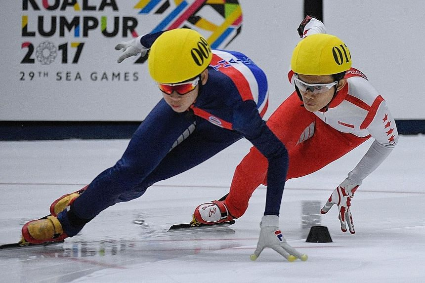 Ice skater Lucas Ng (right) in action during the men's 1,000m speed skating final yesterday. He bagged two silvers at the Games, despite suffering from a serious injury that resulted in his right hand being taped up.
