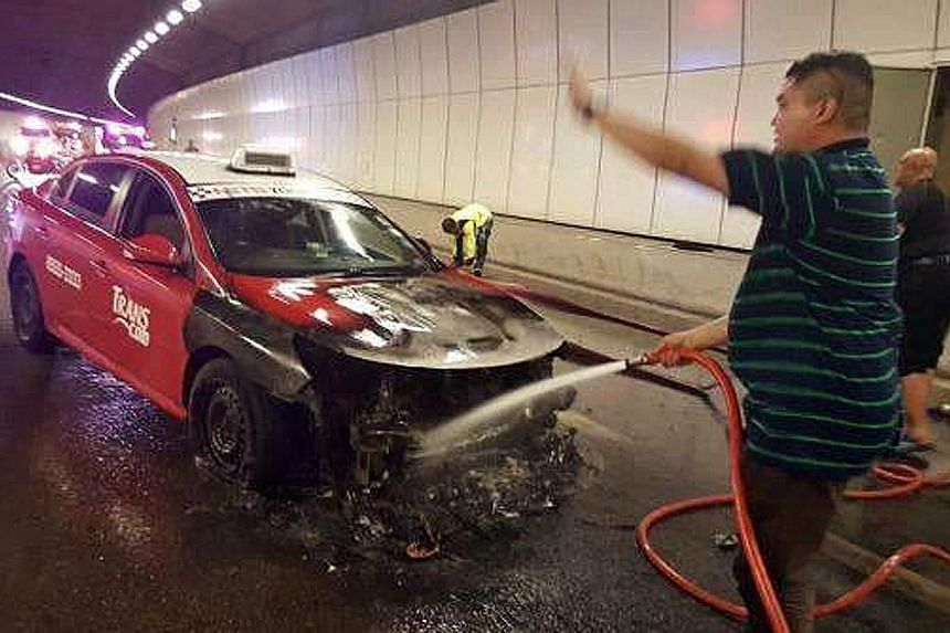 Mr Mohamad Fuad Abdul Aziz (foreground) and Mr Syed Abdillah Alhabshee putting out the taxi fire in the KPE tunnel on Tuesday night.
