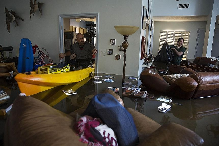 Mr Larry Koser Jr and his son Matthew searching for important papers and heirlooms in their home in the Bear Creek neighbourhood of west Houston, Texas, on Tuesday. The neighbourhood was flooded after water was released from a nearby reservoir.