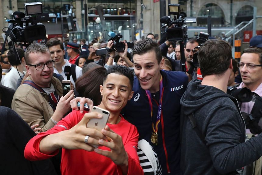 Bosse poses for selfies as he arrives home from the athletics World Championships in London.
