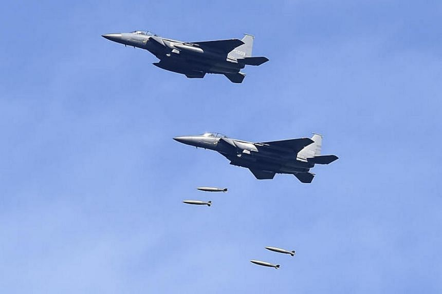 An undated handout photo of F-15K fighter jets with the South Korean military dropping bombs during training at a firing range in South Korea, on Aug 29, 2017.