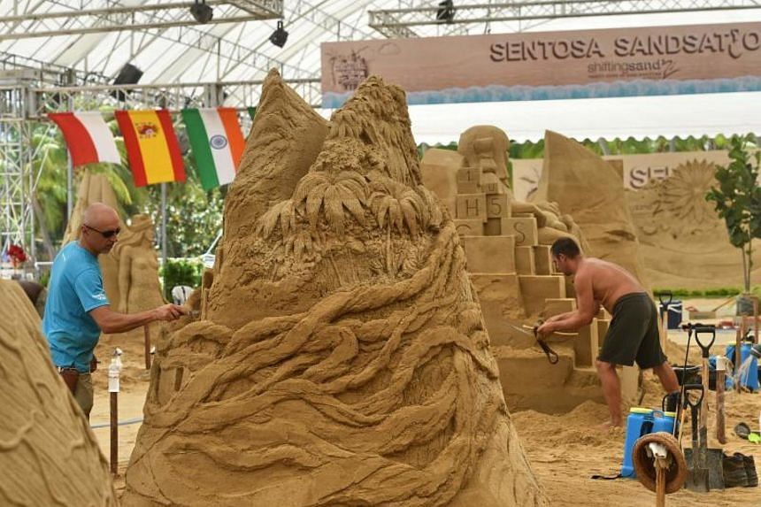Artists work on their sand sculptures while competing during the Sentosa International Sand Sculpting Championship in Singapore on Aug 30, 2017.