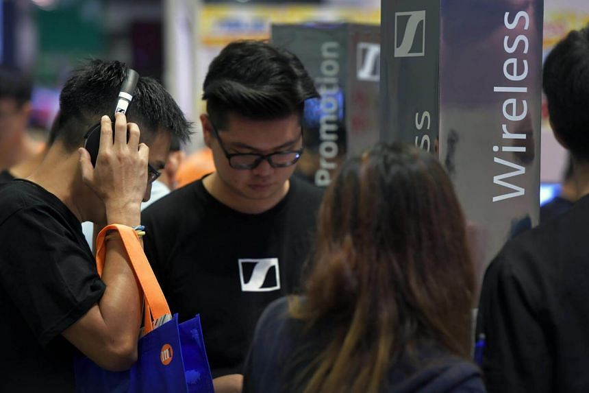 A man tests a pair of headphones on the opening day of the Comex 2017 held at the Suntec City Convention and Exhibiton Centre on Aug 31, 2017.