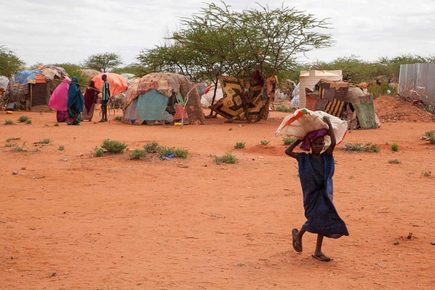 A picture taken on June 9, 2017, in Wender shows a child carrying a bag in a displaced persons camp due to Ethiopia's drought.