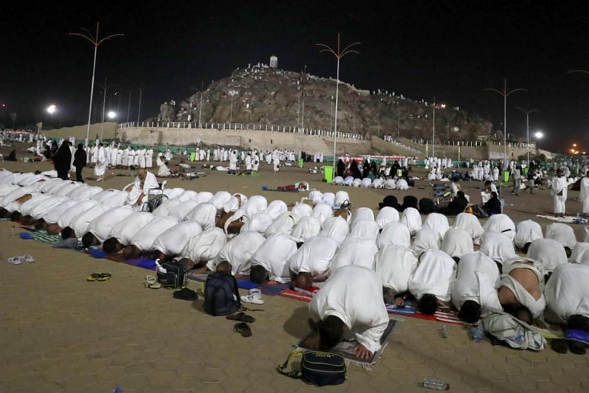 Muslim pilgrims pray near Mount Arafat, also known as Jabal al-Rahma (Mount of Mercy), southeast of the Saudi holy city of Mecca, on Arafat Day which is the climax of the Hajj pilgrimage early on Aug 31, 2017.