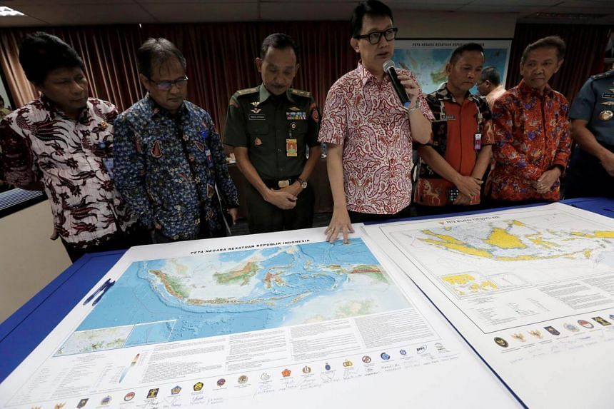 Indonesian Deputy Minister for Maritime Affairs Arif Havas Oegroseno (centre) stands in front of a new map of Indonesia during talks with reporters in Jakarta, Indonesia, July 14, 2017.