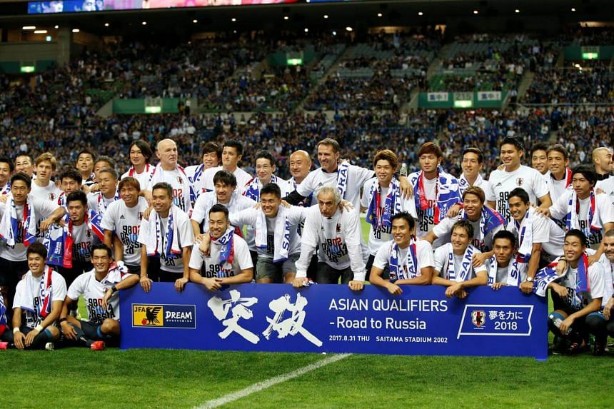 Japan's players pose with a banner after the match.