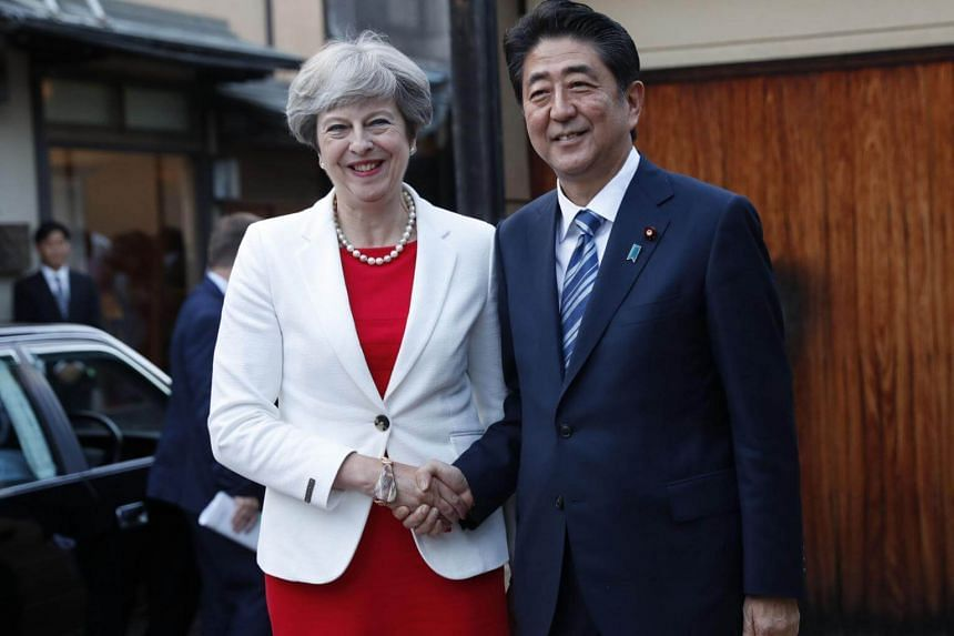 Britain's Prime Minister Theresa May (left) is welcomed by Japan's Prime Minister Shinzo Abe upon her arrival for a tea ceremony at Omotesenke Fushin'an in Kyoto, Western Japan on Aug 30, 2017.