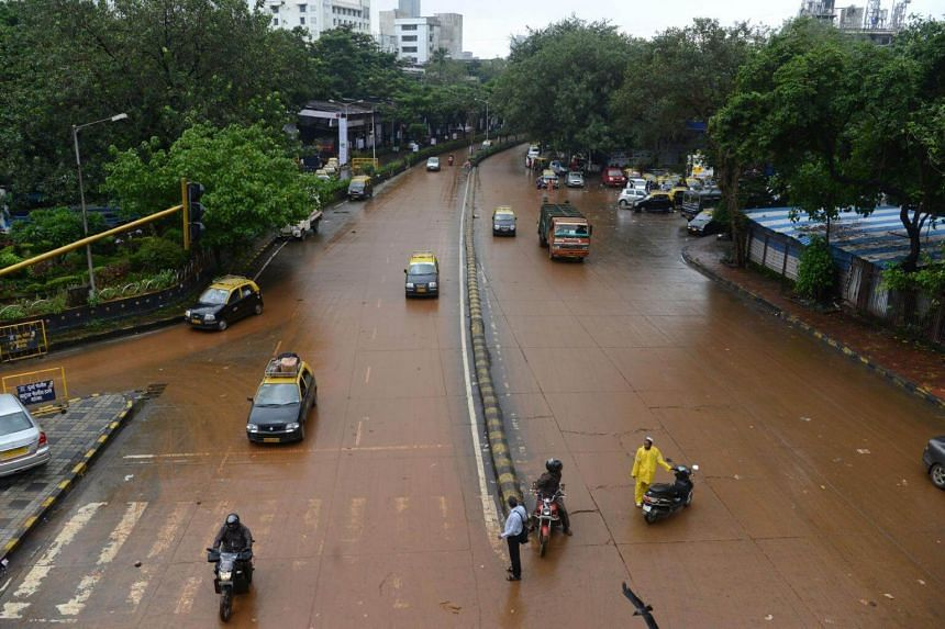Traffic resumes on a muddy road after the water receded in Mumbai following heavy rains that brought major flooding to the coastal city on Aug 30, 2017.