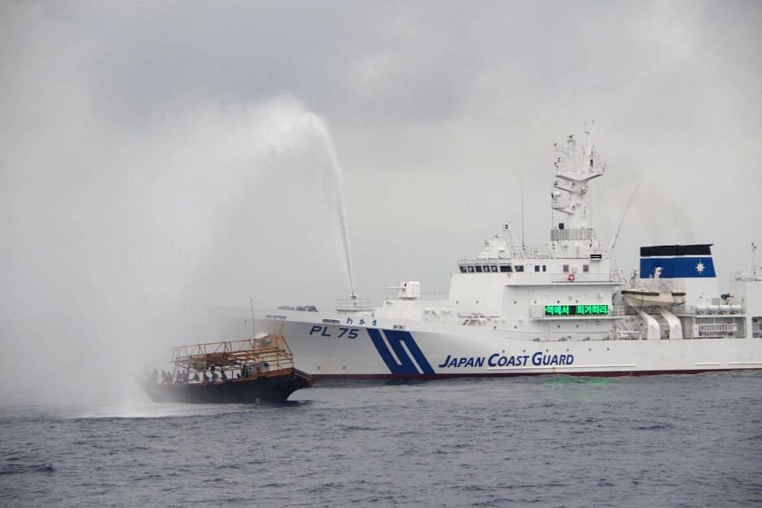 A Japan Coast Guard vessel fires water cannons at a North Korean fishing boat to expel from Japan waters, in Japan's exclusive economic zone at Sea of Japan in a picture taken in July and released on Aug 31, 2017.