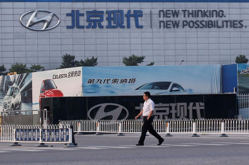 A man walks past a gate of the Hyundai Motor Co plant in Beijing, China, on August 30, 2017.
