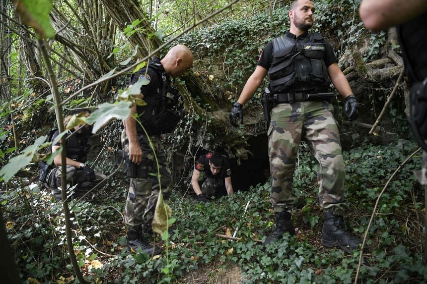 French gendarmes search through a forest around Pont-de-Beauvoisin, eastern france, for Maelys.