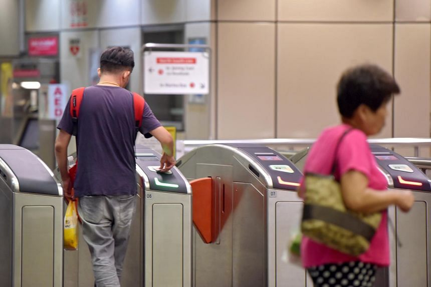 A man tapping out of Braddell MRT Station with his ezLink card.
