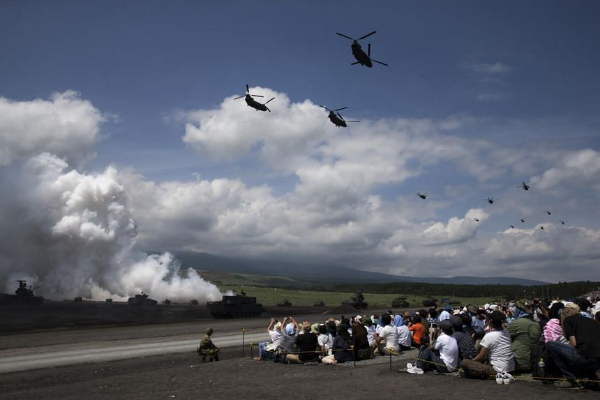 Helicopters fly over spectators watching tanks firing smoke rounds during live-fire drills by Japan's Self-Defense Forces in the foothills of Mount Fuji, on Aug 27, 2017.