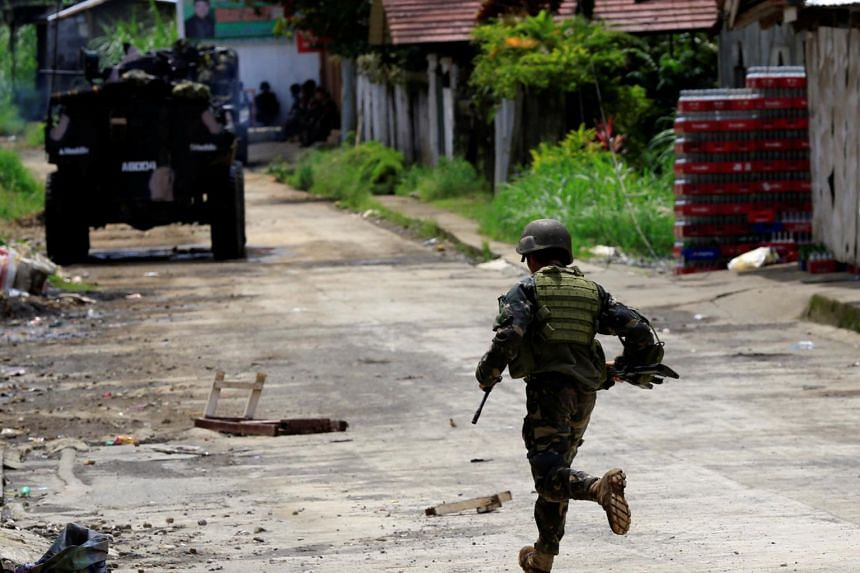 A government soldier runs towards his colleague during government troops assault with insurgents from the so-called Maute group.