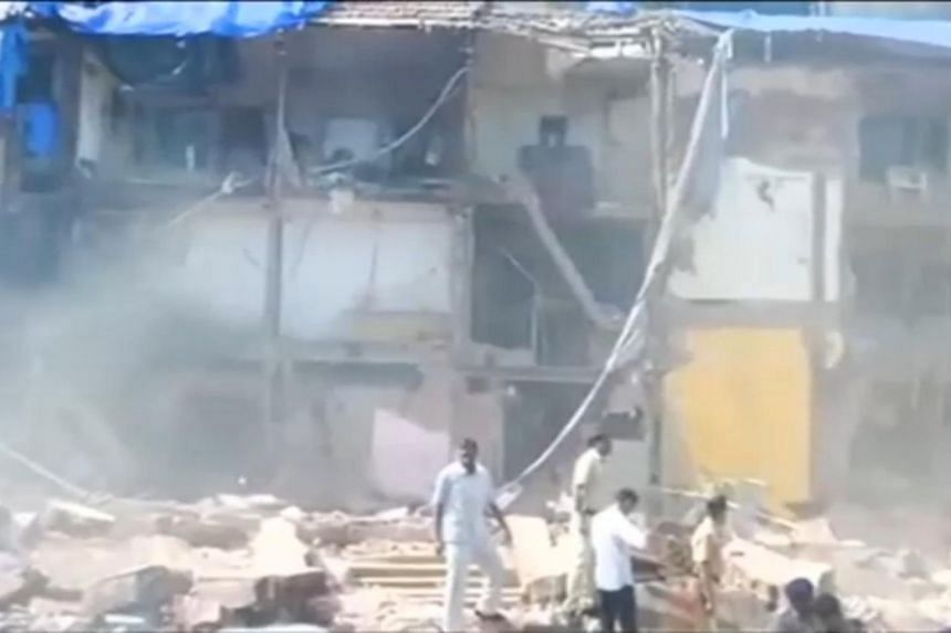 People look on after a building collapsed in Mumbai, India, in this still frame taken from video on Aug 31, 2017.