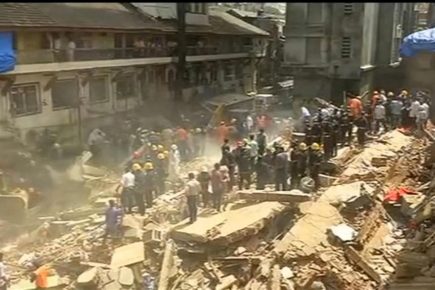 People and rescue personnel are seen after a building collapsed in Mumbai, India, in this still frame taken from video on Aug 31, 2017.