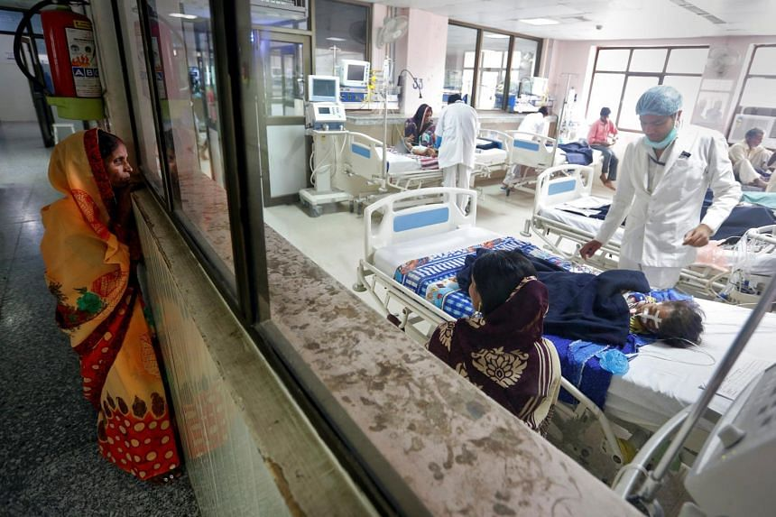 A woman looks into the intensive care unit (ICU) at the Baba Raghav Das hospital in the Gorakhpur district, India.