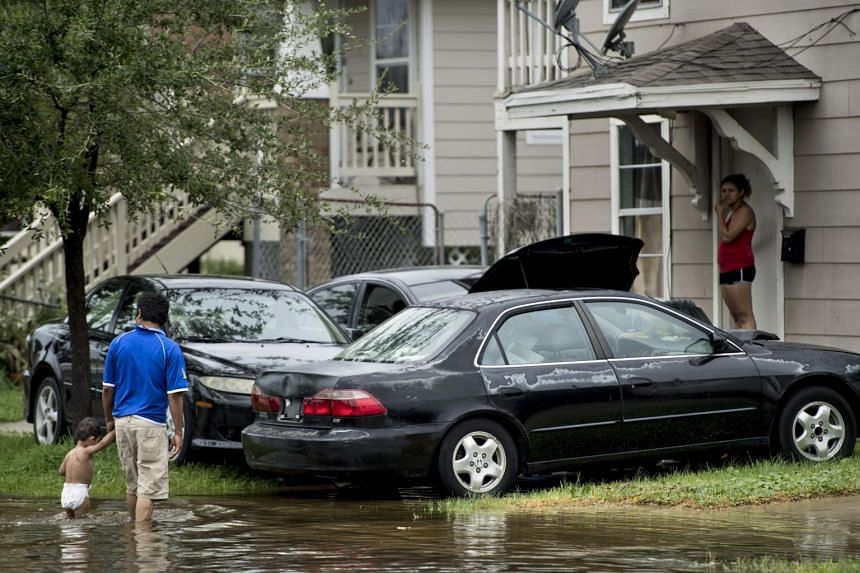 People walk through flooded streets as the effects of Hurricane Harvey are seen Aug 26, 2017 in Galveston, Texas.