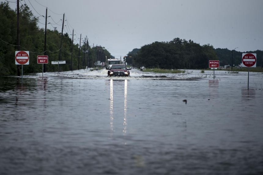 Trucks make their way through flood waters on a main road leading to the Arkema Inc. chemical plant that was in crisis during the aftermath of Hurricane Harvey on Aug 30, 2017 in Crosby, Texas.
