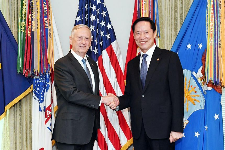 South Korean Defense Minister Song Young Moo (right) shakes hands with US Defense Secretary James Mattis ahead of a meeting at the Pentagon in Washington, DC.
