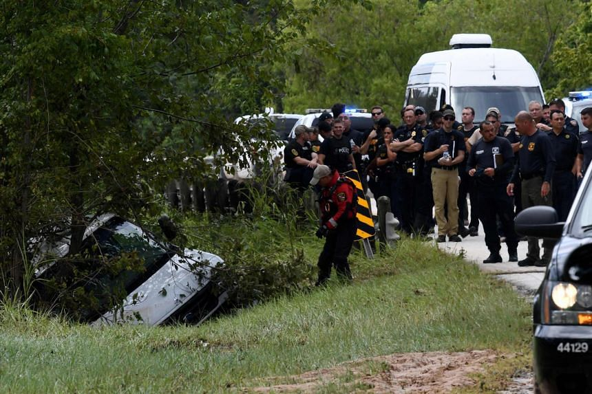 Police investigators watch as the van containing six members of the the Saldivar family who died is towed to the road after they crashed their van into Greens Bayou, while trying to flee Hurricane Harvey during heavy flooding in Houston, Texas.