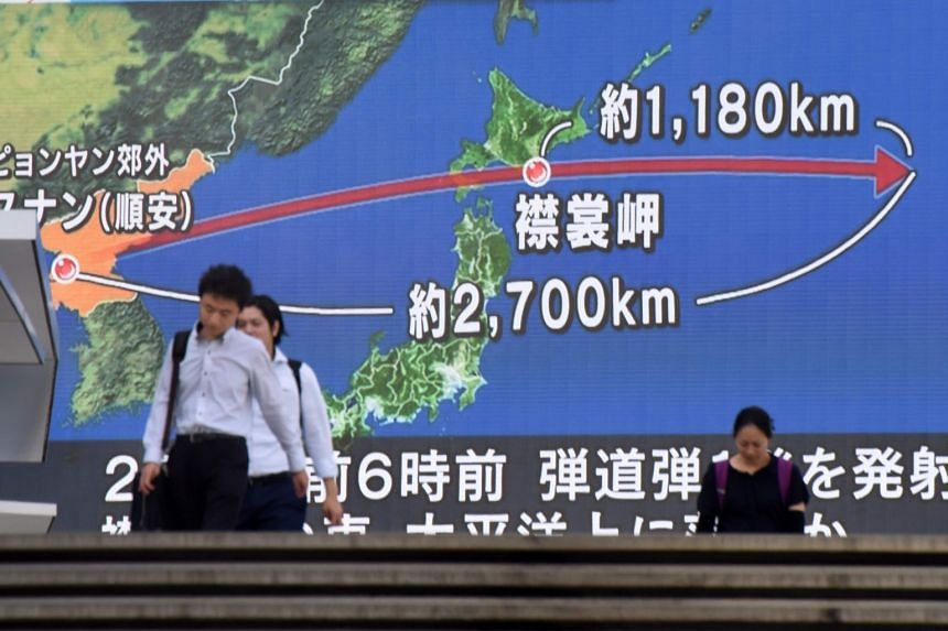 Pedestrians walk in front of a huge screen displaying a map of Japan and the Korean Peninsula, in Tokyo on Aug 29, 2017, following a North Korean missile test that passed over Japan.