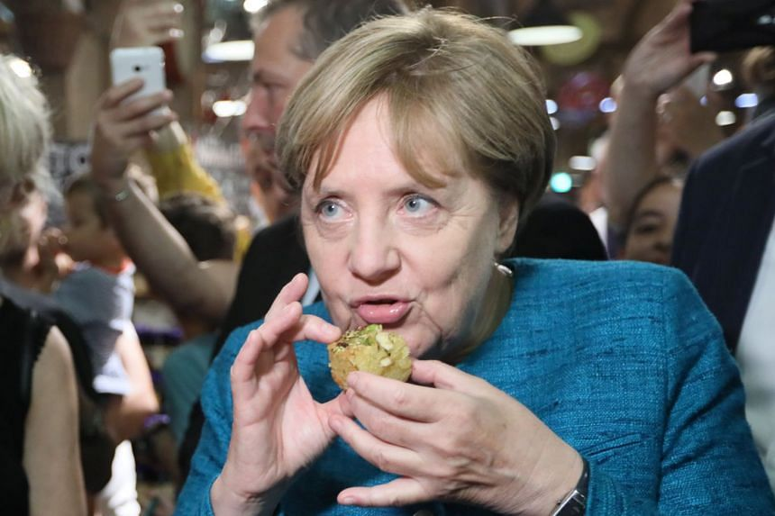 Merkel tastes a Syrian sweet as she campaigns in Roevershagen, Germany, Aug 31, 2017.