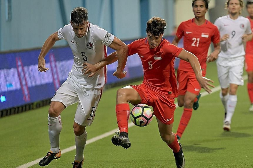 Singapore debutant Ikhsan Fandi (right) keeps the ball as Hong Kong defender Helio Goncalves closes him down. The 18-year-old was a second-half substitute and drew praise from Lions coach V. Sundram Moorthy.
