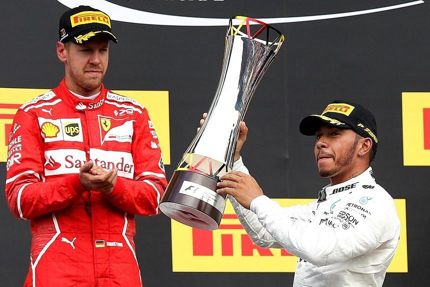 Mercedes' Lewis Hamilton celebrating with the trophy after victory in the Belgian Grand Prix last week as Ferrari's Sebastian Vettel looks on. The Briton will be seeking a record 69th pole at the Italian Grand Prix this weekend and the prospect of ov