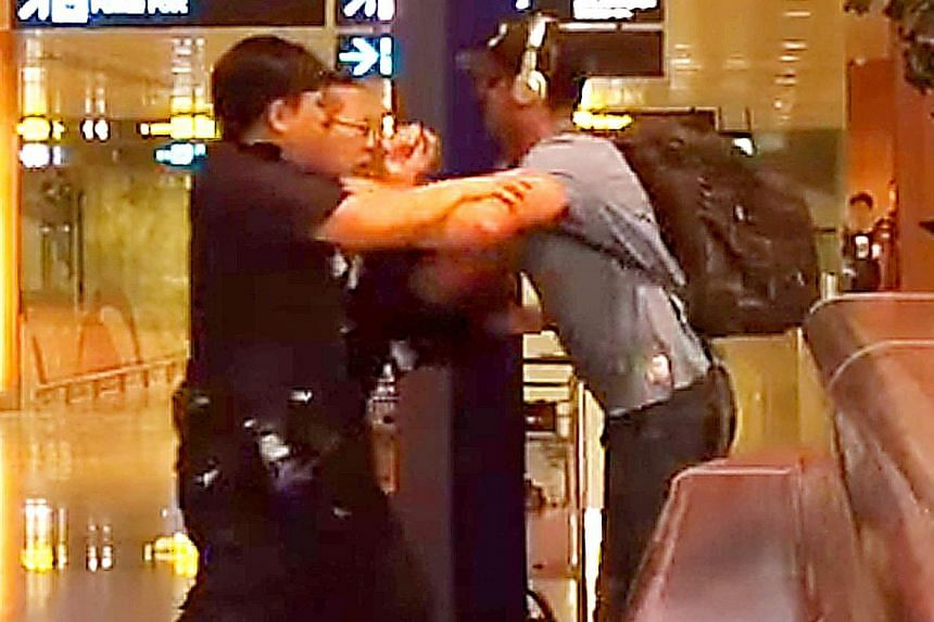 A screenshot from a video showing Jason Peter Darragh, 44, tussling with police at Changi Airport Terminal 2 on April 20.